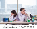 two chemists working in lab... | Shutterstock . vector #1065909725