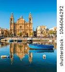 Small photo of Boat and church in Sliema, Malta