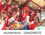 Small photo of group of fans dressed in red color watching a sports event in the stands of a stadium