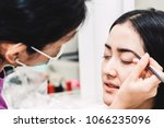 Small photo of Stylist applying apply makeup on a eyebrows to the beautiful woman