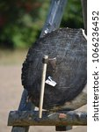 Small photo of Rustic axe throwing target made from a stump of wood with split card demonstrating accuracy.