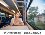 young woman traveling by train | Shutterstock . vector #1066258025
