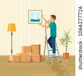 man hanging picture on the wall.... | Shutterstock .eps vector #1066277726