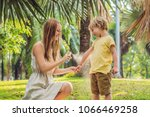 mom and son use mosquito spray... | Shutterstock . vector #1066469258