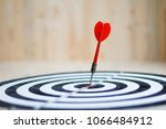 Small photo of Red dart arrow hit the center target of dartboard metaphor marketing competition concept, on wood background