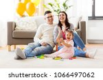 Small photo of family, holidays and people concept - happy mother, father and little daughter clapping hands at home