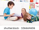 Kids reading a book and having fun together - stock photo