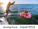 young man jumping off a boat... | Shutterstock . vector #1066679018