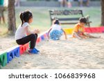 Stock photo little girl sitting lonely watching friends play at the playground the feeling was overlooked by 1066839968