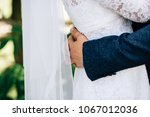 the bridegroom embraces the... | Shutterstock . vector #1067012036