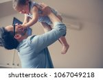 single father with his baby... | Shutterstock . vector #1067049218