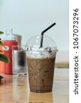 Small photo of Iced mocha with milk froth in plastic cup and cover with black straw on wooden table in cafe. Caffeine in coffee help to fresh in hot day. Relaxing in coffee shop.