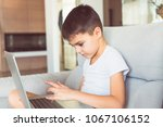 serious boy sitting on sofa ... | Shutterstock . vector #1067106152
