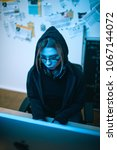Small photo of high angle view of young female hacker developing malware under blue light