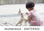 A Child Was Feeding Pigeons.