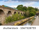 Small photo of Chirk, Wrexham, Wales, UK - August 31, 2016: People steering a narrowboat over the Chirk Aqueduct towards the Chirk Tunnel, with a train passing the Viaduct