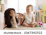 mother and baby playing with... | Shutterstock . vector #1067342522