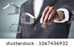 hand holding key with home... | Shutterstock . vector #1067436932