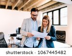 two collegues standing and... | Shutterstock . vector #1067445482