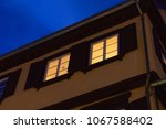 windows facades at blue hour in ... | Shutterstock . vector #1067588402