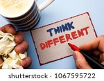 Small photo of Writing note showing Think Different. Business photo showcasing Rethink Change on vision Acquire New Ideas Innovate written by Man on Cardboard Piece Holding Marker on the plain background