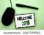 Small photo of Text sign showing Welcome 2018. Conceptual photo Celebration New Celebrate Future Wishes Gratifying Wish written on Sticky Note Paper on the plain background Pen and Mouse next to it.