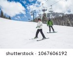 a young skier and a snowboarder ... | Shutterstock . vector #1067606192