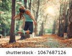 woman doing star jump outdoors... | Shutterstock . vector #1067687126