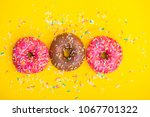 sweet donuts with sprinkles on... | Shutterstock . vector #1067701322