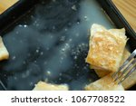 Small photo of close up baked tose pouring with syrup and milk placing on black dish,dessert after lunch.