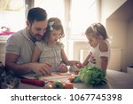 father with his daughters... | Shutterstock . vector #1067745398
