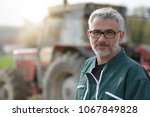 Farmer Standing By Tractor...