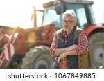 farmer standing by tractor... | Shutterstock . vector #1067849885