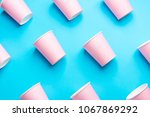 Small photo of Pattern from Pink Paper Drinking Cups Arranged Diagonally on Mint Blue Backgrounds. Birthday Party Celebration Abstract Fashion Baby Shower Concept. Pastel Colors. Minimalist Style