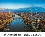 Small photo of London, England - Panoramic aerial skyline view of London including Tower Bridge with red double-decker bus, Tower of London, skyscrapers of Bank District and Shard skyscraper at golden hour