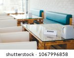 white reserved sign on a table... | Shutterstock . vector #1067996858