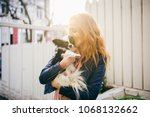Stock photo a young red haired caucasian woman holds a small funny dog in the arms of two colors of black and 1068132662