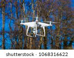 drone soars in front of trees... | Shutterstock . vector #1068316622