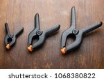 black plastic clamps on a wood... | Shutterstock . vector #1068380822