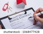 human hand filling rental... | Shutterstock . vector #1068477428