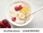 porridge with banana yoghurt ... | Shutterstock . vector #1068580082