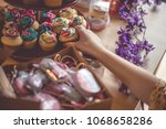 Small photo of Everyone loves sweet treats. Rainbow icing, pretty colors, and floral designs on cupcakes. Pretty cupcake tower display with purple flowers and a lovely macaron treat box.