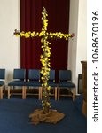 Small photo of Lent cross decorated for Easter Sunday, adorned with bright daffodils and two red roses to signify the nails