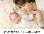 Small photo of Mother and newborn daughter lie on pink plaid. They are dressed in warm knitted white sweaters. Maternal love and care. Hairpin lies next to them