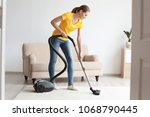 Young Woman Cleaning Carpet...