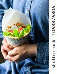 Small photo of Greek pita gyros or souvlaki pita in women hands. Traditional street fast food with meat, tomato, fried potatoes, lettuce and sauce. Denim dress in background, place for text