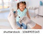 doctor filling syringe with... | Shutterstock . vector #1068905165