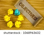 Small photo of Text sign showing Objectives Motivational Call. Conceptual photo Goals planned to be achieved Desired targets written on Folded Cardboard Paper piece on wooden background Crumpled Paper Balls.