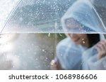 rainy day asian woman wearing a ...   Shutterstock . vector #1068986606