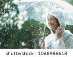 rainy day asian woman wearing a ... | Shutterstock . vector #1068986618